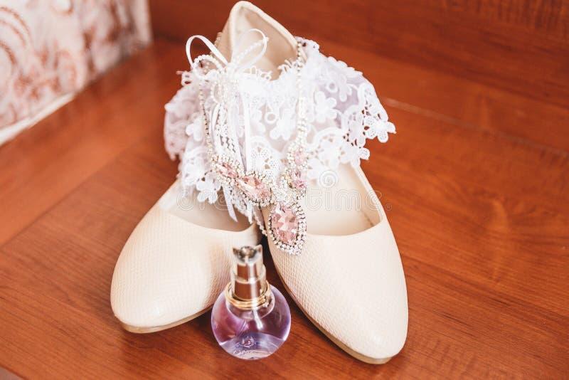 Witte Huwelijksschoenen en kousebandbruid stock fotografie