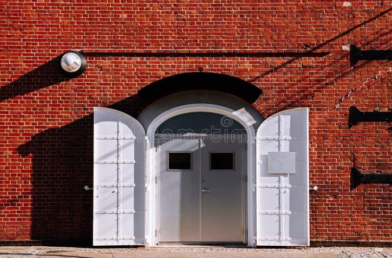 Witte ijzeren poort met rode bakstenen wand, oud loft warehouse royalty-vrije stock afbeeldingen