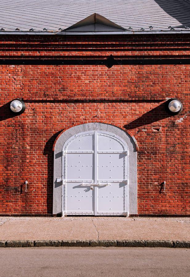 Witte ijzeren poort met rode bakstenen wand, oud loft warehouse stock foto's