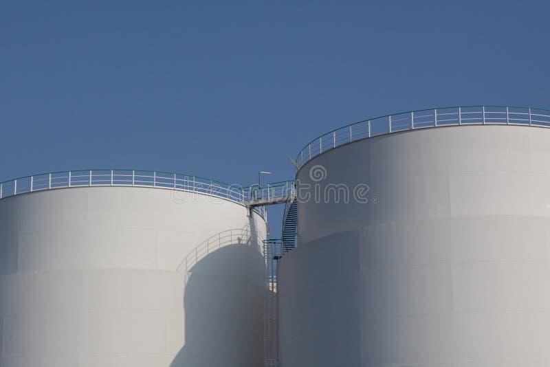 Witte industriële opslagtanks bij stedelijke haven stock afbeelding