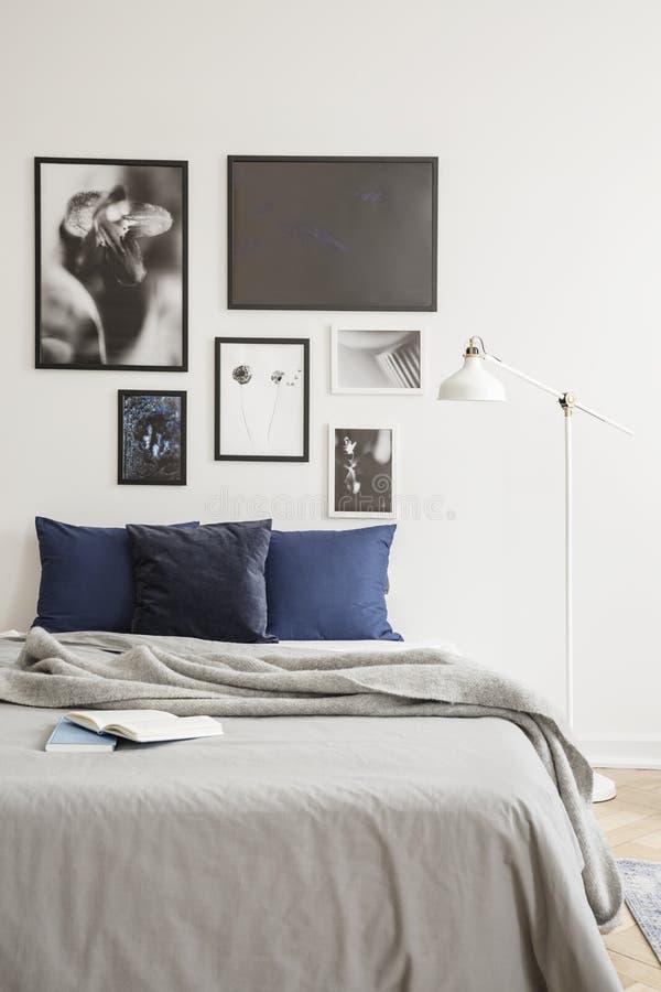 Witte industriële stijlstaande lamp door een comfortabel bed met donkerblauwe kussens in een heldere hipsterslaapkamer royalty-vrije stock fotografie