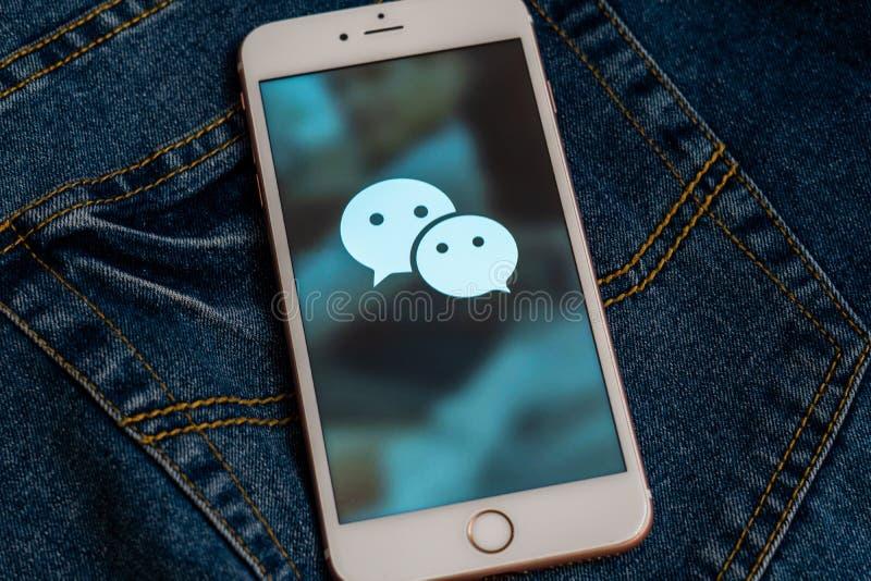 Witte iPhone met embleem van sociale media WeChat van China op het scherm Sociaal media pictogram stock foto