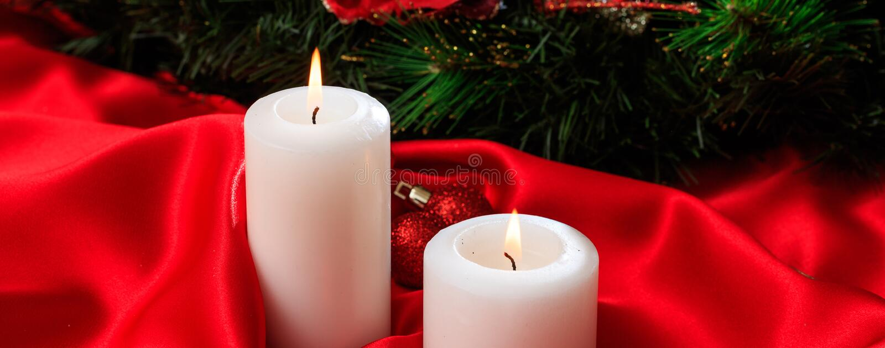Witte kaarsen bij het rode satijn branden op een donkere achtergrond, banner stock fotografie