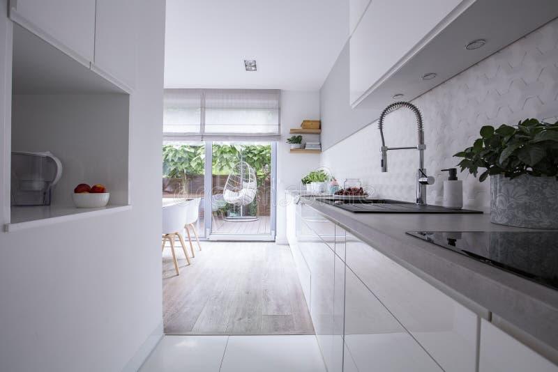 Witte kabinetten in helder modern keukenbinnenland van huis met terras Echte foto royalty-vrije stock afbeeldingen