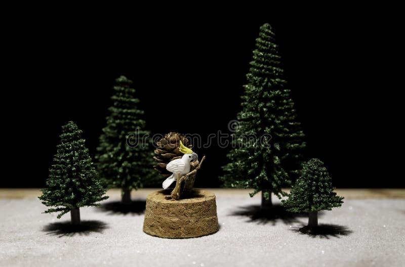 Witte Kaketoetribune op tak onder groene die Kerstboom van zwarte achtergrond wordt geïsoleerd stock fotografie