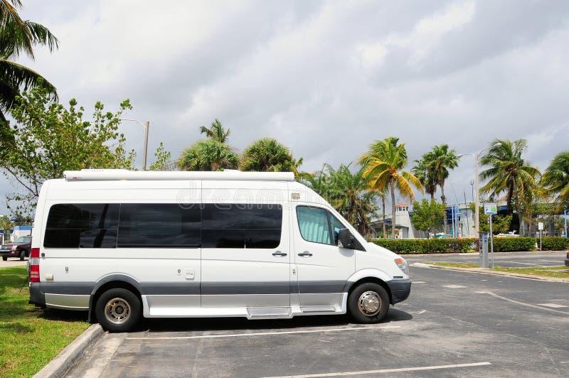 Witte kampeerautobestelwagen in parkeerterrein royalty-vrije stock fotografie