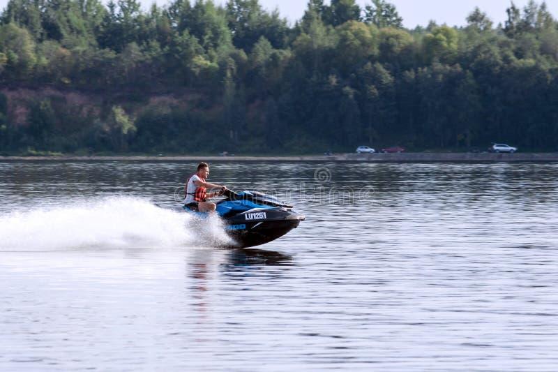 Witte, Kaukasische aantrekkelijke mens op een blauwe watermotorfiets stock foto's