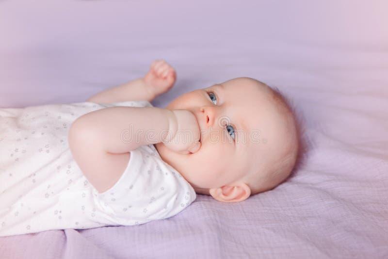 witte Kaukasische het meisjesjongen van het zuigelingskind met blauwe ogen die op bed liggen die zuigende vingersvuist likken royalty-vrije stock afbeeldingen