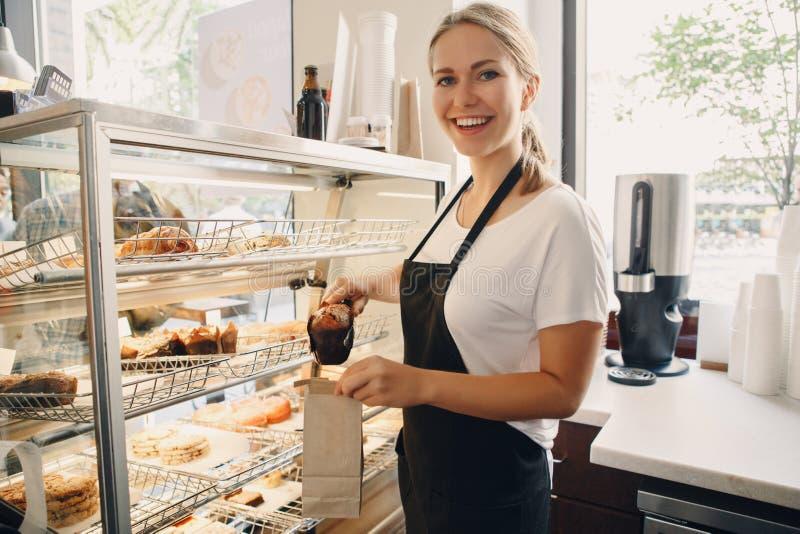 witte Kaukasische mooie baristavrouw die muffingebakje van shop-window nemen royalty-vrije stock afbeeldingen