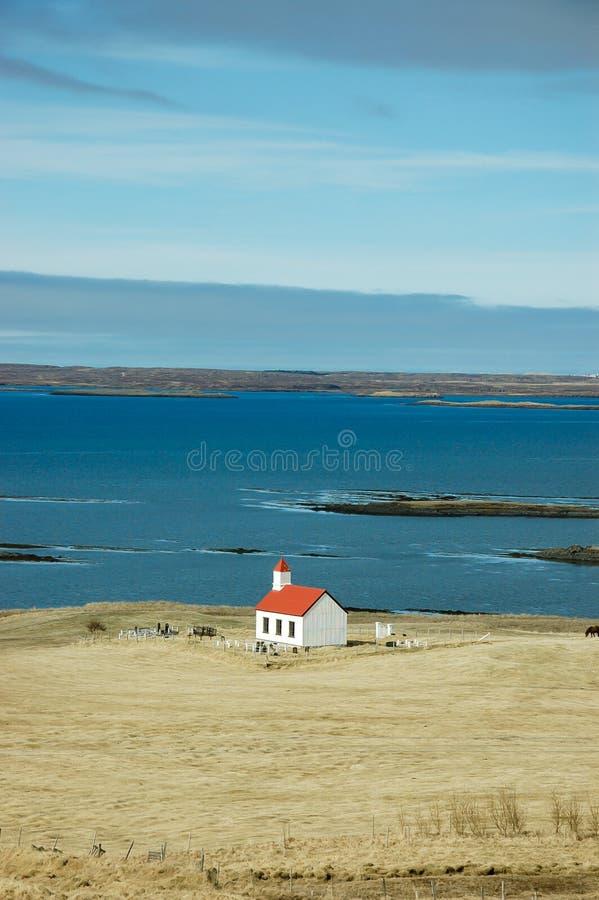 Witte kerk, turkooise overzees, hayfield, IJsland stock afbeelding