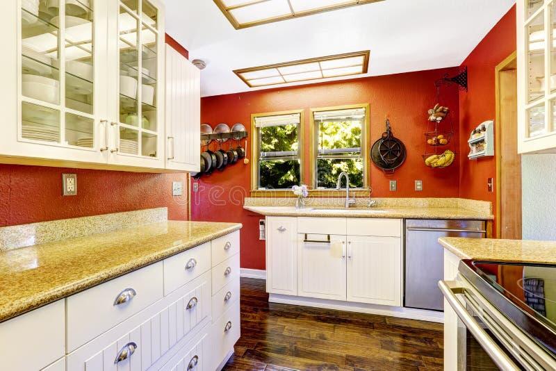 Witte keukenruimte met contrast heldere rode muren stock foto's