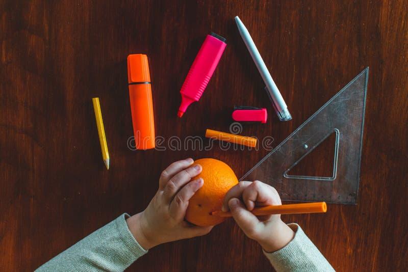 Witte kleine handen van een Kaukasische tekening van het peuterkind met een oranje potlood op een oranje fruit royalty-vrije stock foto's