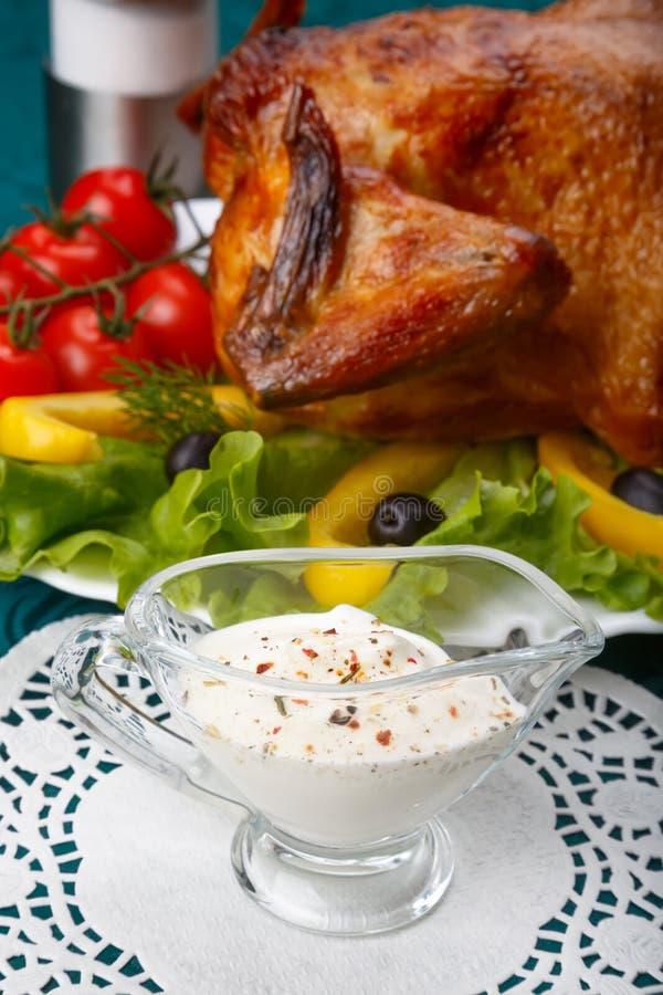 Witte knoflooksaus voor gehele geroosterde kip stock fotografie