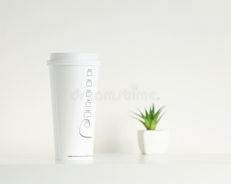 Witte koffiekop en groene ingemaakte installatie stock foto's