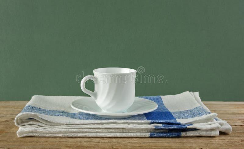 Witte koffiekop en theedoek op oude houten lijst over groene bedelaars royalty-vrije stock foto