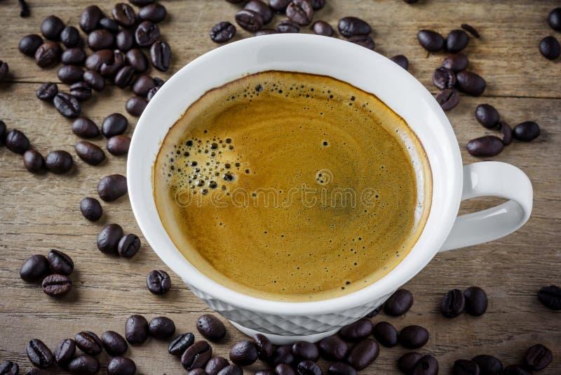 Witte koffiekop met koffiebonen stock afbeeldingen