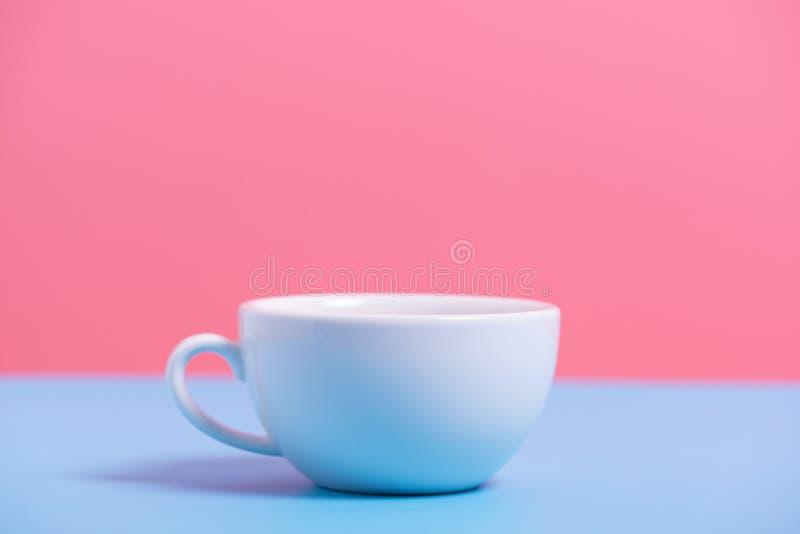 Witte koffiekop op blauw en roze document, minimale stijlbackgrou royalty-vrije stock afbeeldingen