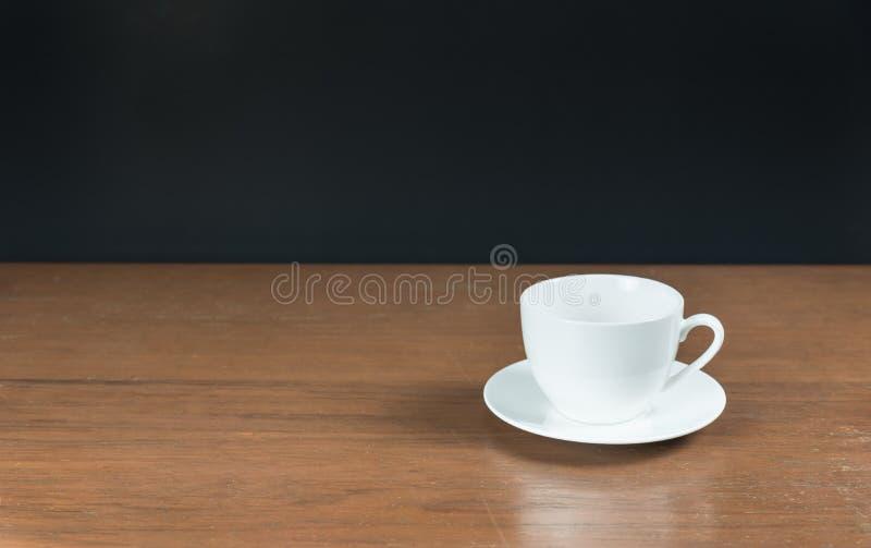 Witte koffiekop op een lijst met zwarte achtergrond stock fotografie