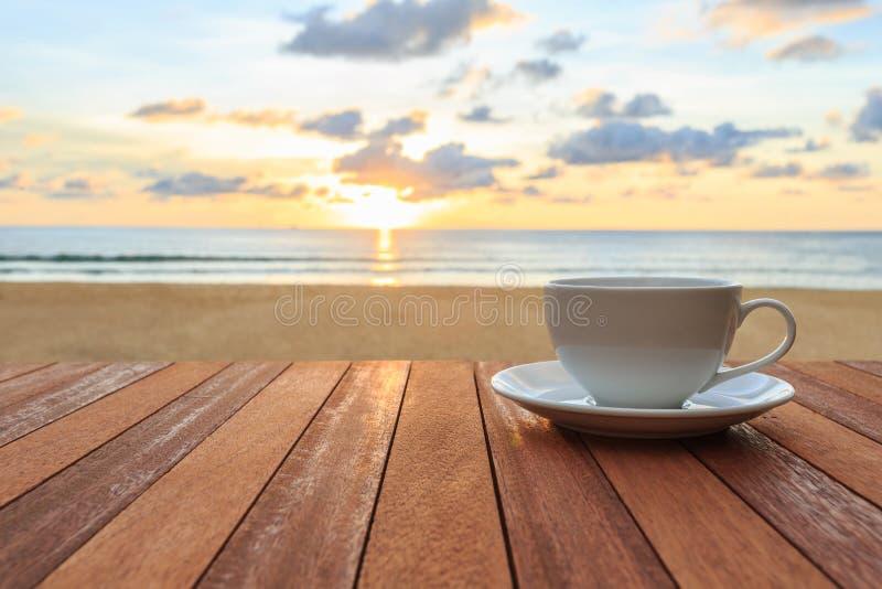 Witte koffiekop op houten lijst en mening van zonsondergang of zonsopgangbac royalty-vrije stock fotografie