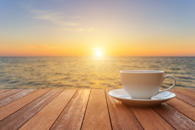 Witte koffiekop op houten lijst en mening van zonsondergang of zonsopgangbac royalty-vrije stock foto's