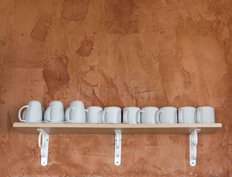 Witte koffiekoppen die op houten plank met achtergrond van het grunge de oranje cement plaatsen stock foto's