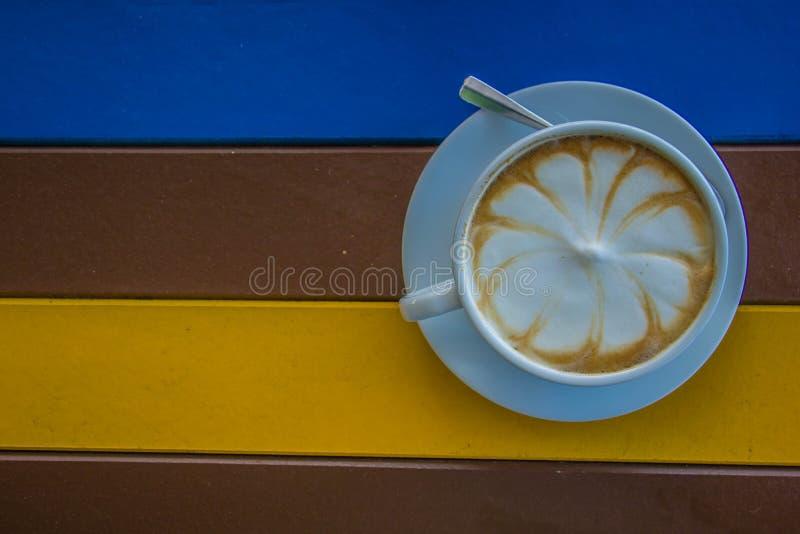 Witte koffiemok op kleurrijke houten lijst royalty-vrije stock fotografie