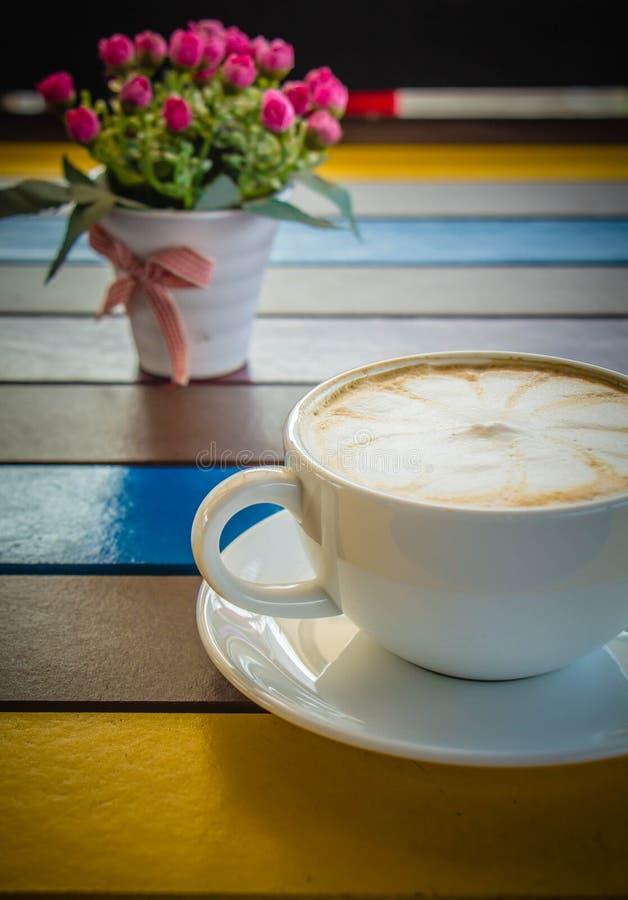Witte koffiemok op kleurrijke houten lijst stock fotografie
