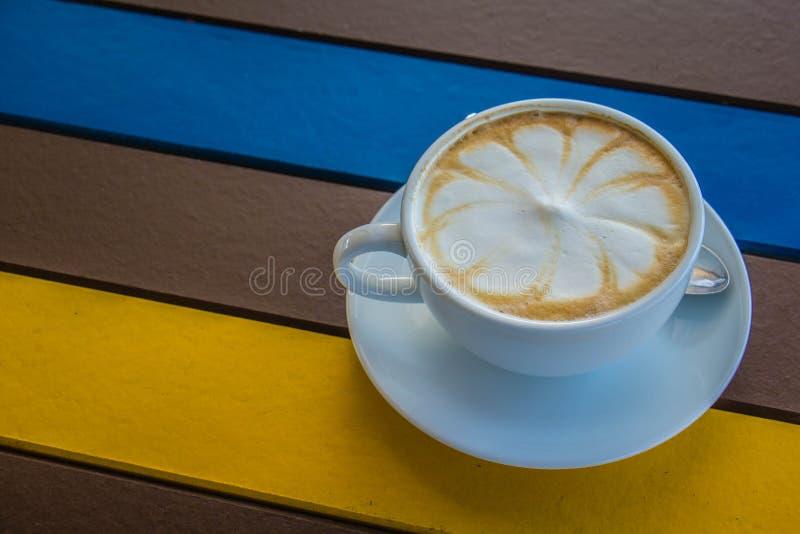 Witte koffiemok op kleurrijke houten lijst royalty-vrije stock afbeeldingen