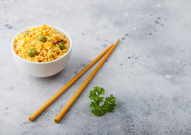 Witte kom met gekookte organische basmati-plantaardige rijst met houten stokjes op een lichte achtergrond Gele maïs en groene erw stock afbeeldingen