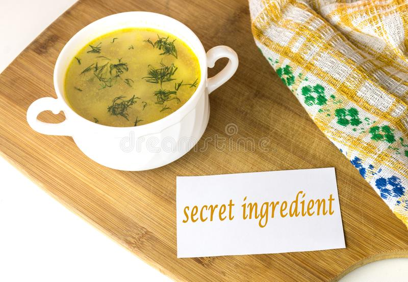 Witte kom met gele kippensoep met groene dille met een nota 'geheim ingrediënt ' stock foto
