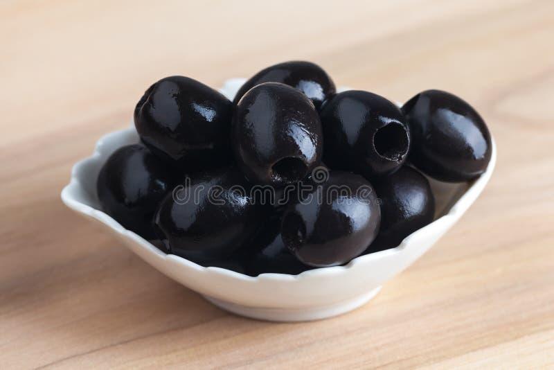 Witte kom met zwarte olijven op houten lijst stock foto