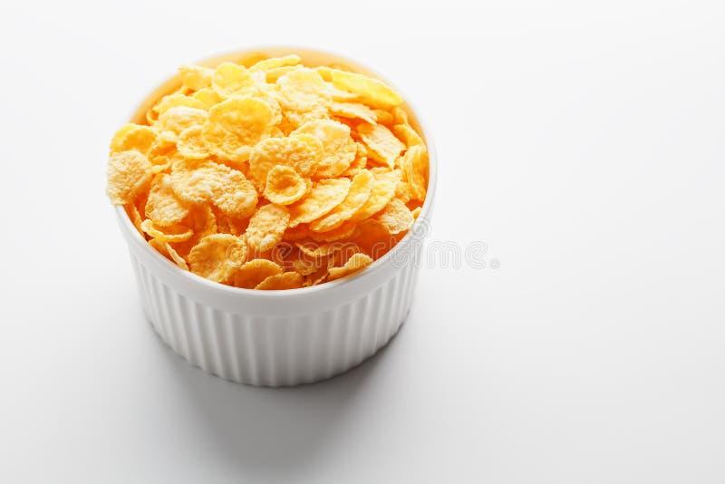 Witte kop met gouden die cornflakes op witte achtergrond worden ge?soleerd Mening van hierboven Heerlijk en gezond ontbijt stock fotografie