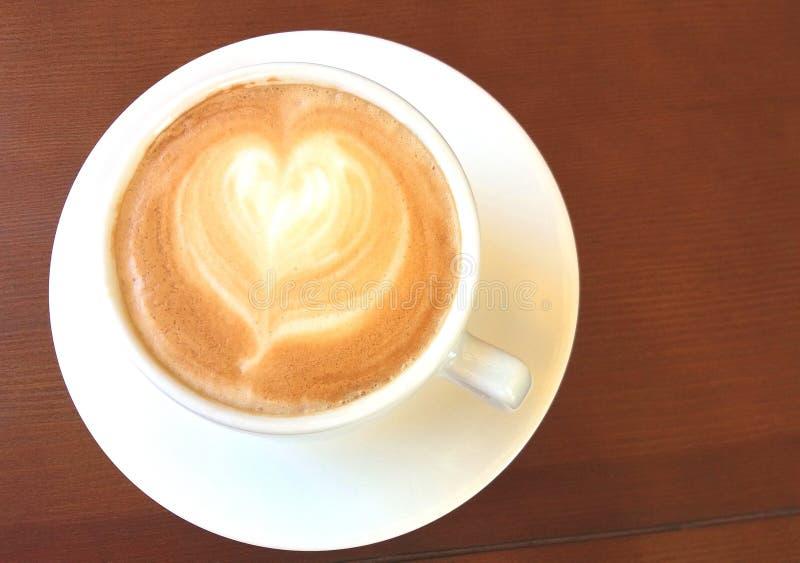 Witte kop met Italiaanse cappuccinokoffie met patroon in de vorm van mooie hart dichte omhooggaand op houten achtergrond royalty-vrije stock fotografie