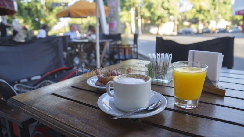 Witte kop met koffie met melk en glas jus d'orange op een houten lijst buiten een restaurant op een zonnige ochtend stock fotografie