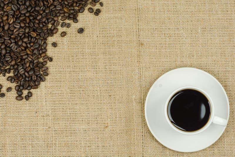 Witte kop met koffiedrank op juteachtergrond stock foto