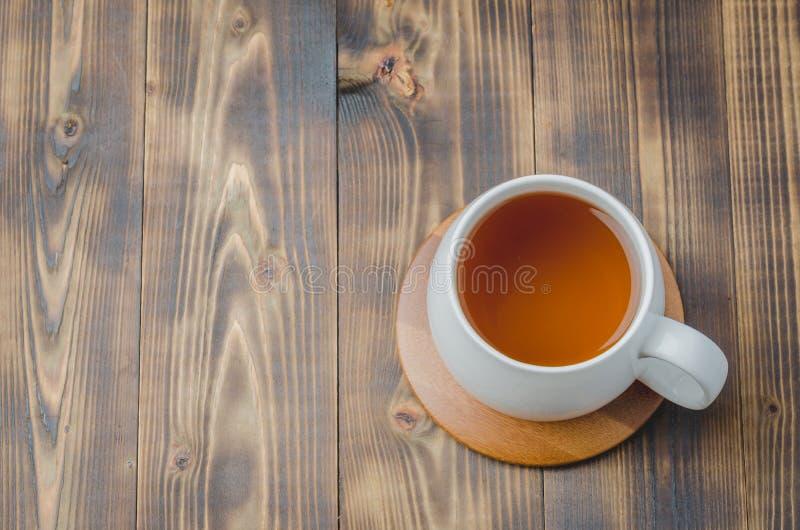 witte kop met thee op een bamboesteun op een houten lijst, hoogste mening, copyspace royalty-vrije stock fotografie