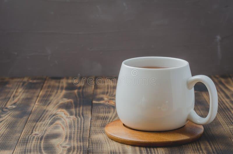 witte kop met thee op een bamboesteun op een houten lijst, selectieve nadruk, copyspace royalty-vrije stock afbeeldingen