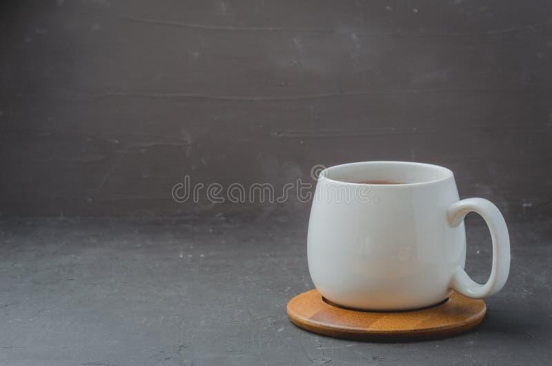 witte kop met thee op een bamboesteun op een zwarte steenlijst, copyspace stock afbeelding