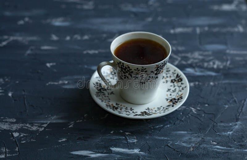 Witte kop met zwarte koffie op een donkere achtergrond stock fotografie