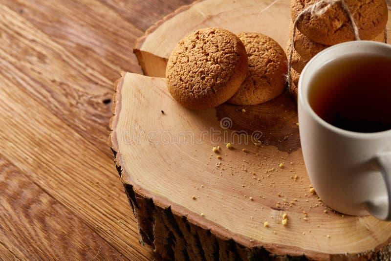 Witte kop thee en koekjes op een logboek over de stijl houten achtergrond van het land, close-up, selectieve nadruk royalty-vrije stock afbeelding