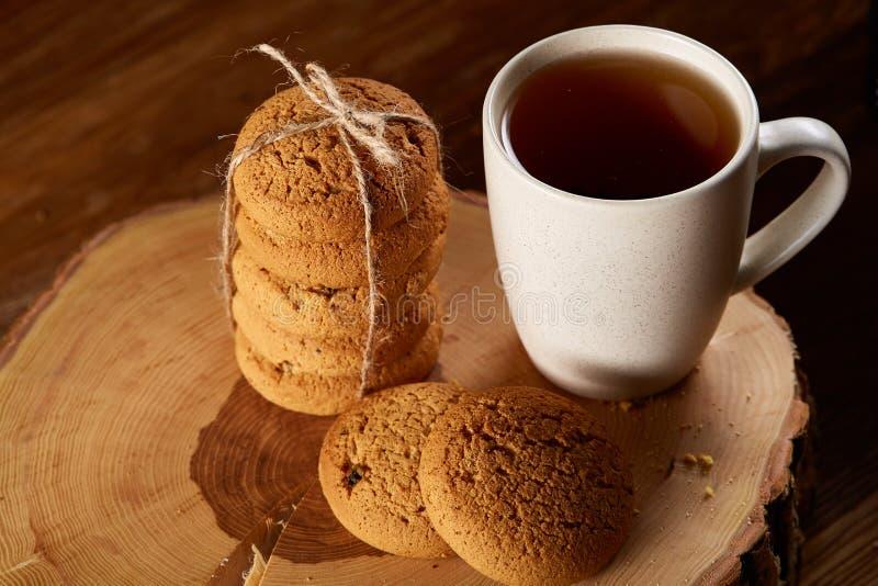 Witte kop thee en koekjes op een logboek over de stijl houten achtergrond van het land, close-up, selectieve nadruk royalty-vrije stock fotografie