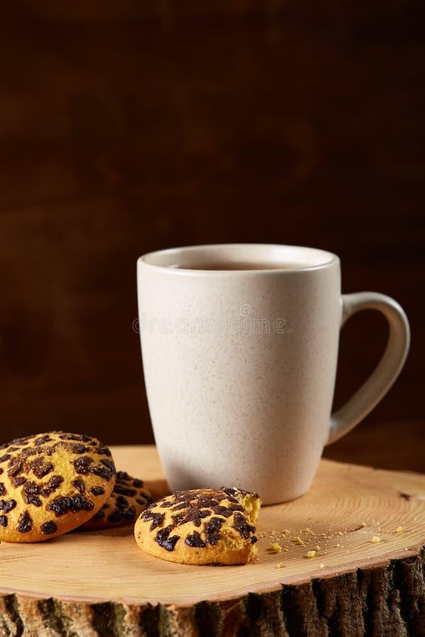 Witte kop thee en koekjes op een logboek over de stijl houten achtergrond van het land, close-up, selectieve nadruk stock foto