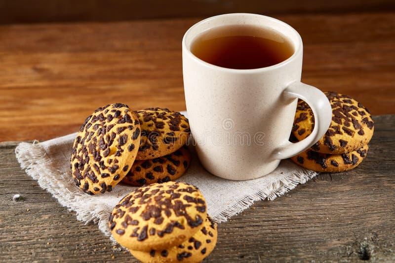 Witte kop thee en koekjes op een logboek over de stijl houten achtergrond van het land, close-up, selectieve nadruk stock afbeeldingen