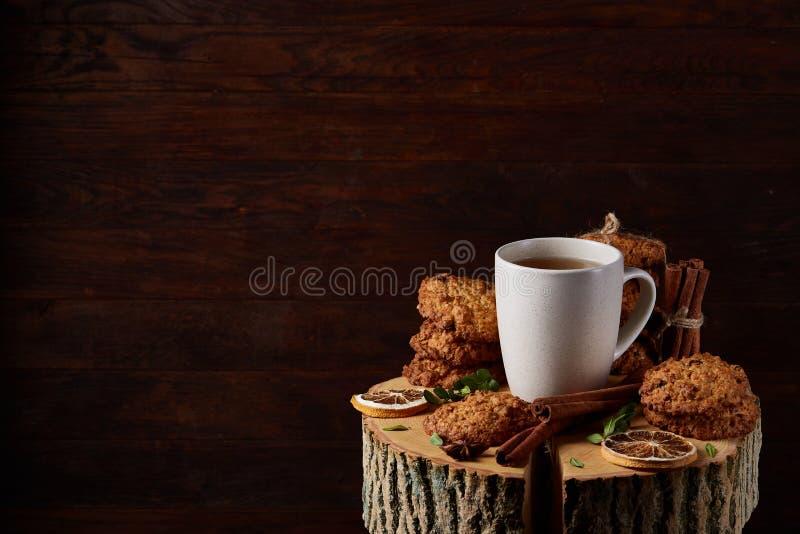 Witte kop thee en koekjes op een logboek over de stijl houten achtergrond van het land, close-up, selectieve nadruk royalty-vrije stock foto
