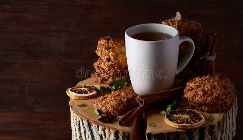 Witte kop thee en koekjes op een logboek over de stijl houten achtergrond van het land, close-up, selectieve nadruk royalty-vrije stock foto's