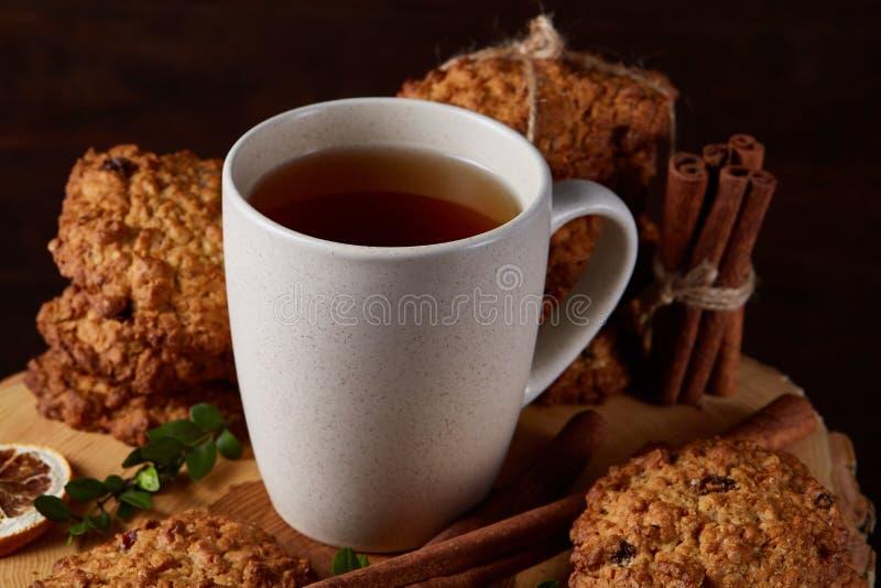 Witte kop thee en koekjes op een logboek over de stijl houten achtergrond van het land, close-up, selectieve nadruk royalty-vrije stock afbeeldingen