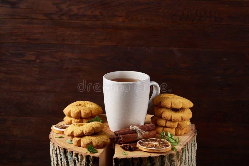 Witte kop thee en koekjes op een logboek over de stijl houten achtergrond van het land, close-up, selectieve nadruk stock afbeelding