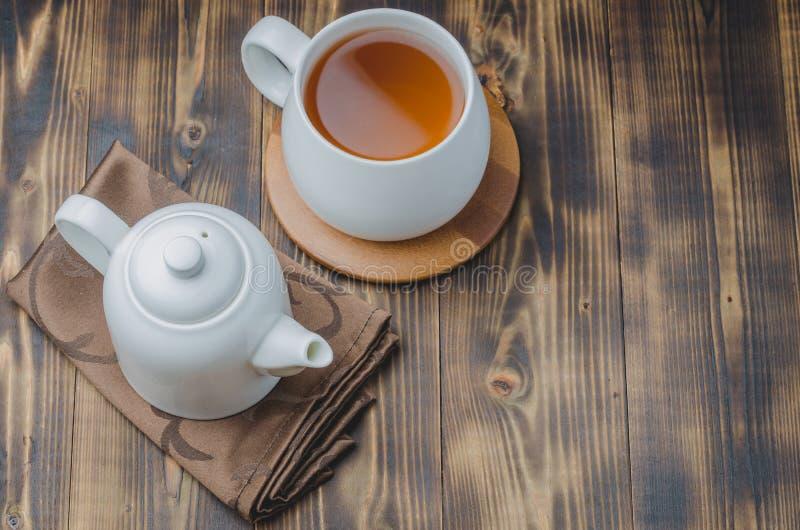 witte kop thee en theepot op een zwarte houten achtergrond, hoogste mening en copyspace royalty-vrije stock afbeeldingen
