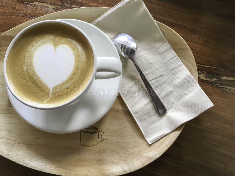 Witte kop van de cappuccinokoffie van de hartvorm op houten plaat stock fotografie