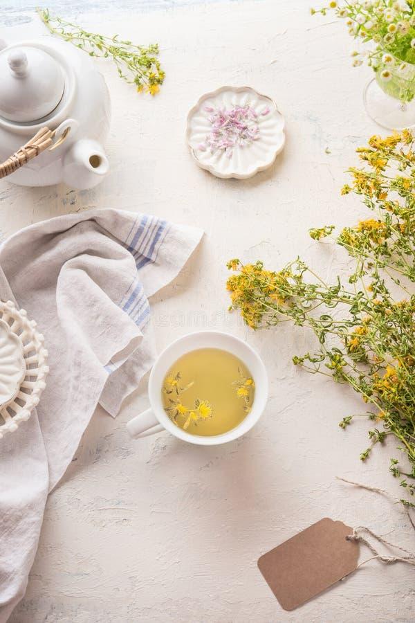 Witte kop van geel aftreksel op lichte lijst met theepot en verse kruiden en bloemen Organische Tutsan-thee o stock afbeeldingen